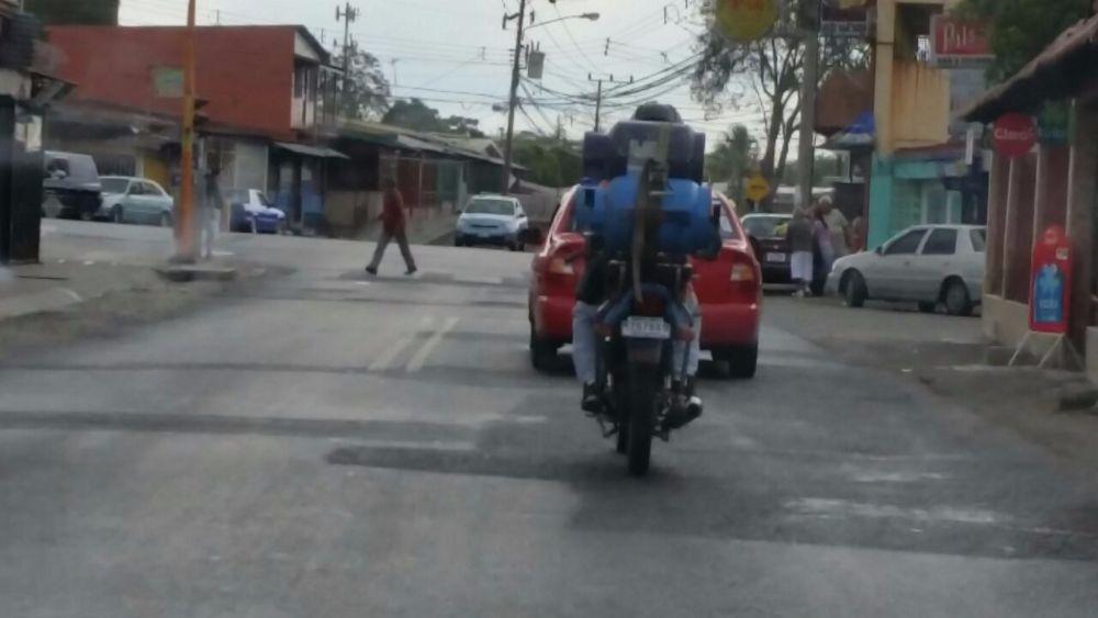 Motociclista se las ingenia para trasladar tres cilindros de gas, Tránsito señala infracción