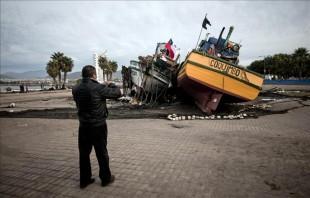 Fotografía tomada el pasado 19 de septiembre en la que se registró a un hombre al fotografiar dos barcos arrastrados a la vía Costanera, por el sismo del pasado 16 de septiembre de 2015, en la localidad costera de Coquimbo (Chile). EFE/Archivo